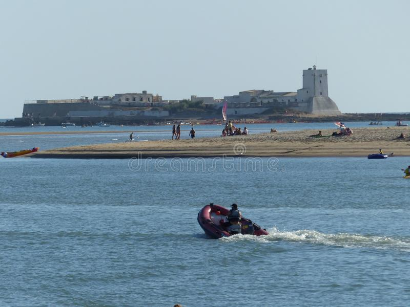 Een vesting op een eilandje op het overzees met in de voorgrond een vlot in beweging in Andalusia Spanje royalty-vrije stock afbeelding