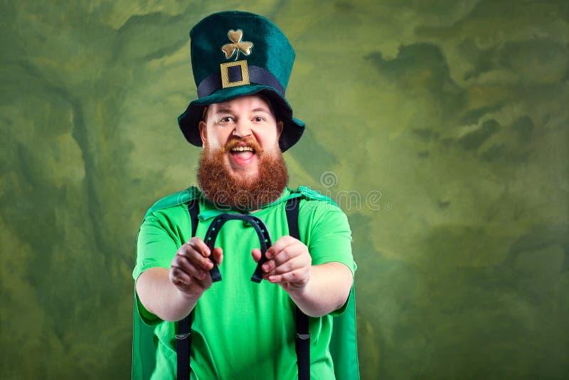 Een vette mens met een baard in het kostuum van St Patrick glimlacht een paard stock fotografie