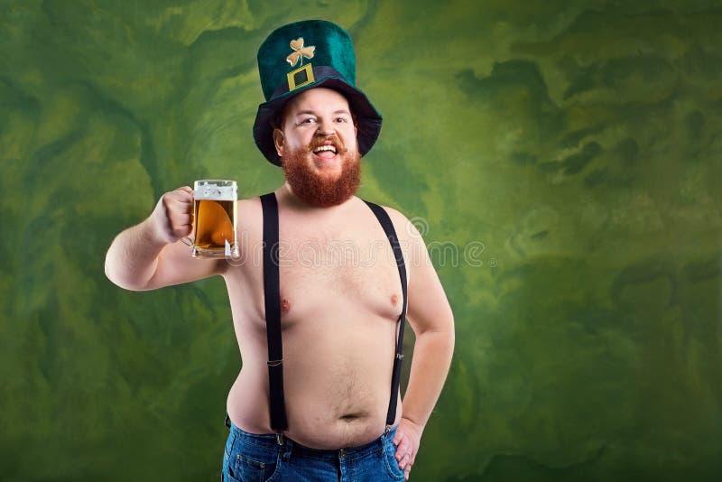 Een vette mens met een baard in St Patrick ` s kostuum glimlacht met A.M. stock fotografie