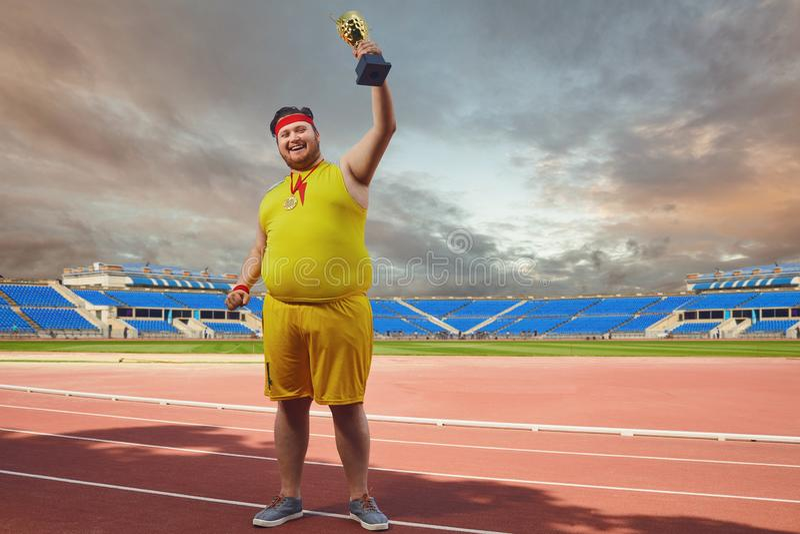 Een vette mens met de kop van een winnaar in zijn handen bij het stadion stock afbeelding