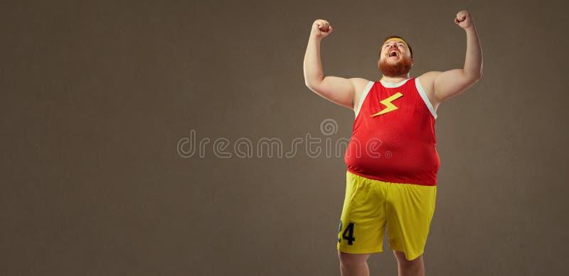Een vette mens in sportenkleren gilt bij de overwinning stock afbeelding