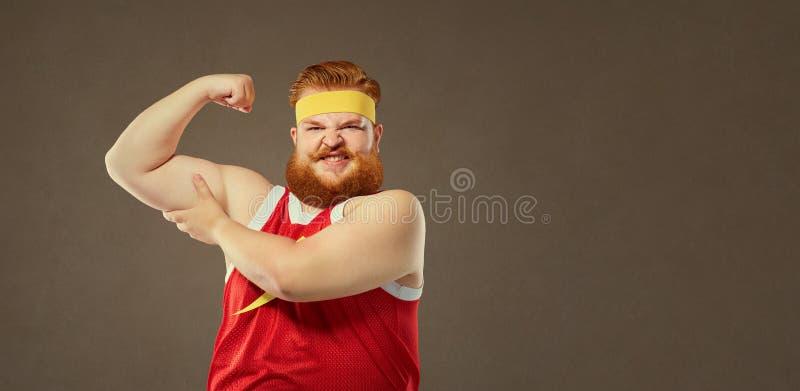 Een vette mens in een sportkostuum houdt zijn spieren op zijn wapen royalty-vrije stock foto's