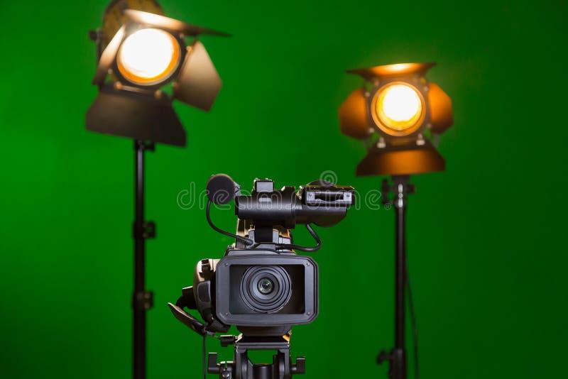 Een videocamera en een schijnwerper met een Fresnel lens op een groene achtergrond Film in het binnenland De chromasleutel stock foto