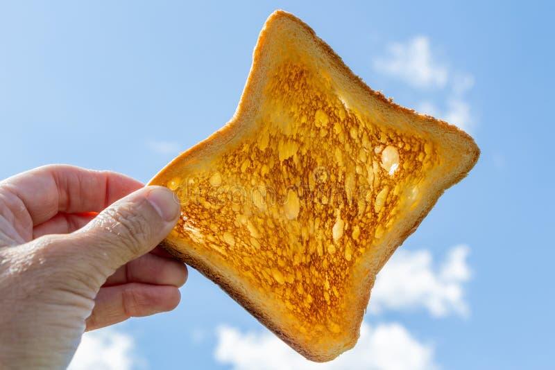 Een vierkant blozend stuk van brood voor toost in een linkervrouwenhand tegen de blauwe hemel met witte wolken op picknick in de  stock fotografie