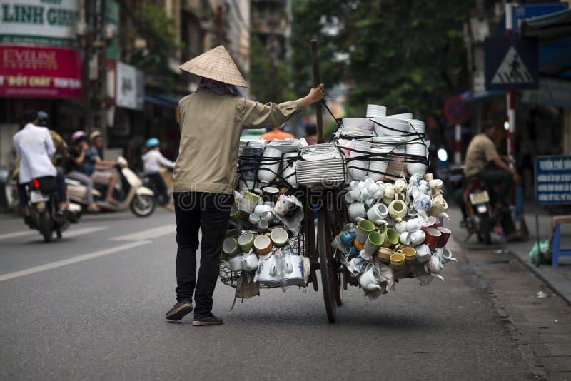 Een Vietnamese verkoper die haar fietshoogtepunt van porseleingoederen duwen voor verkoop in een straat van Hanoi, Vietnam Straat stock fotografie