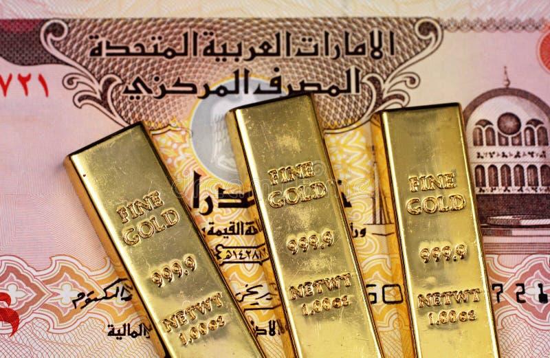 Een vijf dirhambankbiljet van de Verenigde Arabische Emiraten met drie kleine goudstaven stock afbeelding