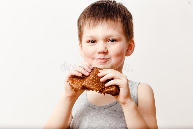 Een vijf-jaar-oude Russische jongen in een grijze t-shirt eet een oliepannekoek op een witte achtergrond Maslenitsa royalty-vrije stock fotografie