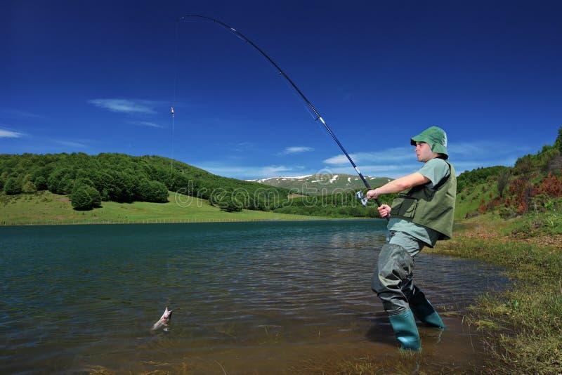 Een visser die op een meer Mavrovo vist royalty-vrije stock fotografie