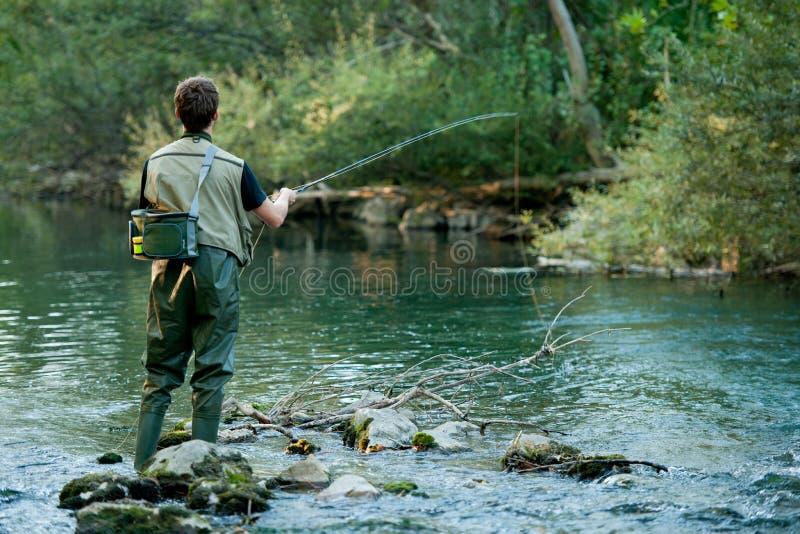 Een visser die op een rivier vist royalty-vrije stock foto's