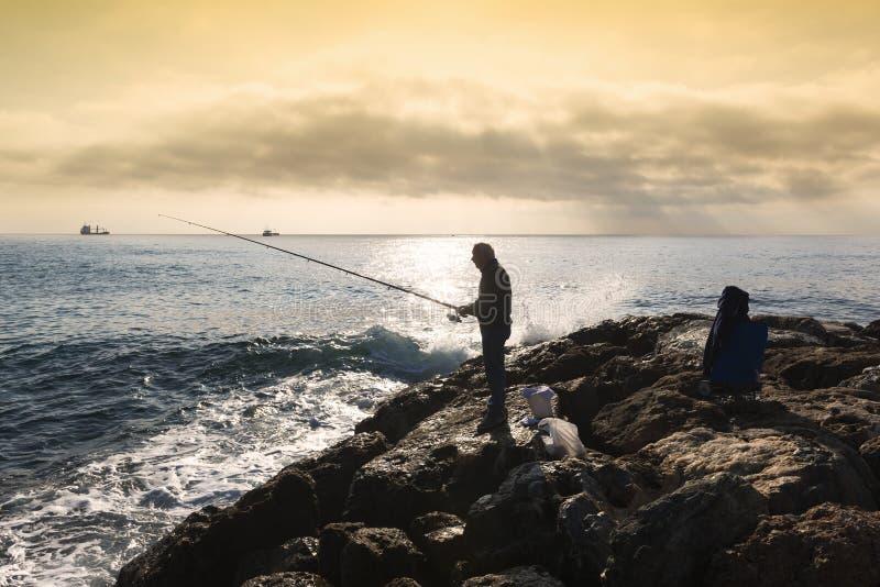 Een visser die zich met de hengel in zijn hand bevinden, is hij royalty-vrije stock foto's