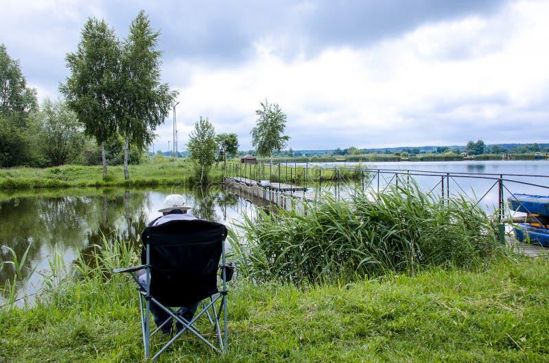 Een visser in een GLB zit als voorzitter dichtbij het meer met een hengel en vangt vissen royalty-vrije stock afbeelding