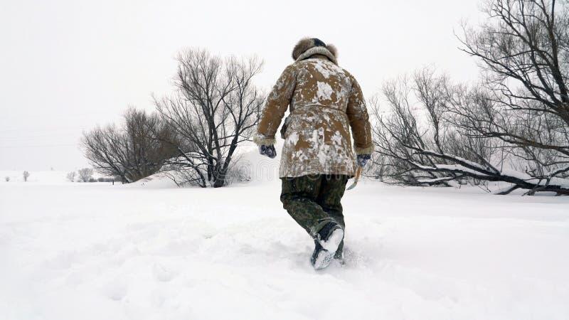 Een visser loopt op een snow-covered meer op zoek naar een goede visserijplaats stock fotografie