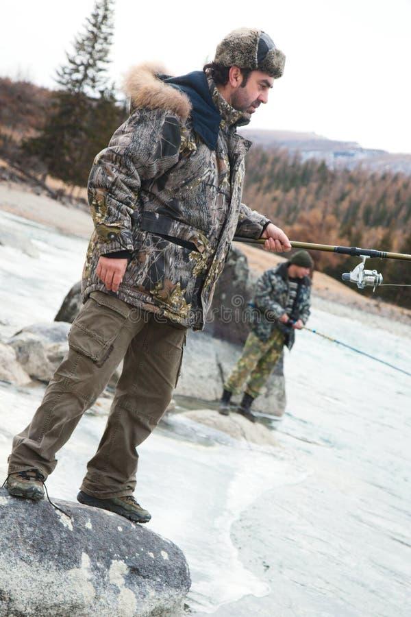Een visser op de rivier in de winter stock afbeelding