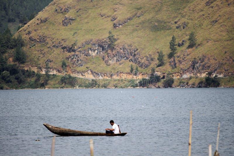 Een visser op het midden van laut tawar meer stock foto
