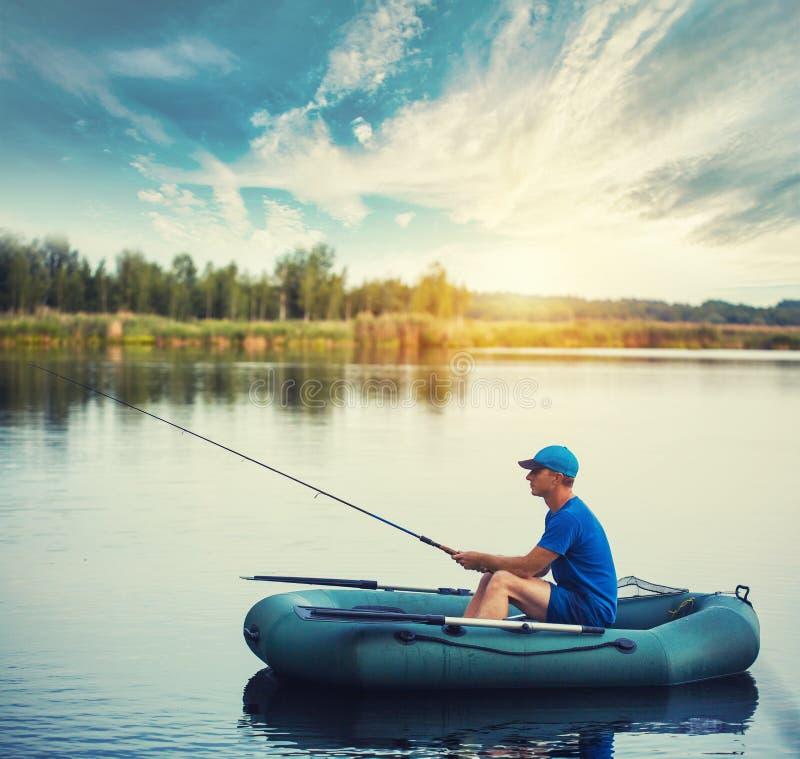 Een visser in een rubberboot vist op het meer stock foto's
