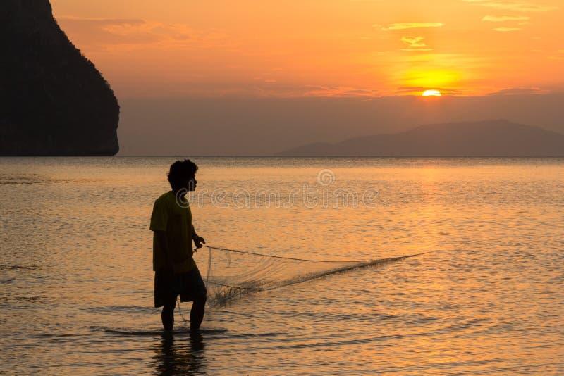 Een visser trekt in zijn net bij zonsondergang op Rajamangala-strand in Trang-provincie, Thailand royalty-vrije stock foto's