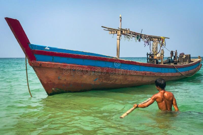 Een visser waadt uit in taille diep water aan zijn kleurrijke houten boot van het strand in Ngapali, Myanmar stock fotografie