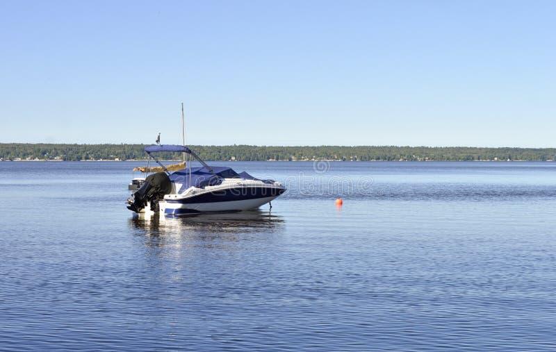 Een vissersboot of de snelheidsboot zitten voor een zeilboot royalty-vrije stock afbeeldingen