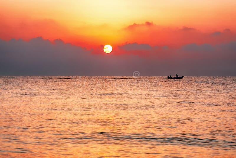 Een vissersboot in de stralen van de het plaatsen zon stock foto's
