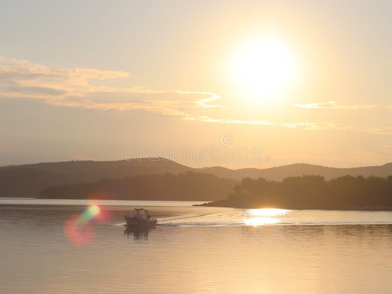 Een vissersboot kruist de overzeese baai in de ochtendzon Dawn bij de toevlucht Zware menselijke arbeid Rust en rust na overzeese stock afbeelding