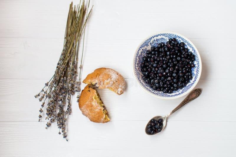 Een vlakte legt van een bosbessenmuffin, een bosbessenkom en bloemen van lavendel op een witte achtergrond royalty-vrije stock afbeeldingen