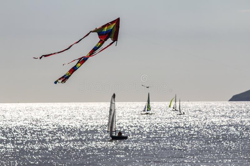 Een vlieger vliegt hoog boven de jachten die van Kiezelachtig Hoofd dichtbij Eastbourne in Oost-Sussex, Engeland varen royalty-vrije stock afbeeldingen