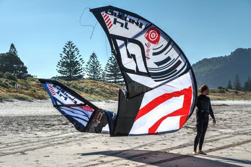 Een vliegersurfer die zich op het strand met zijn vlieger bevinden stock afbeeldingen