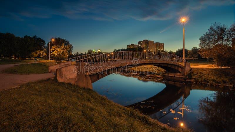 een voet concrete brug met metaalleuningen over wordt een smalle rivier in het de stadspark van de de herfstavond verlicht door h royalty-vrije stock foto