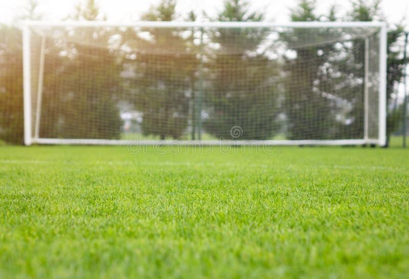 Een voetbal netto met schot in helder zonlicht met bomen stock foto's