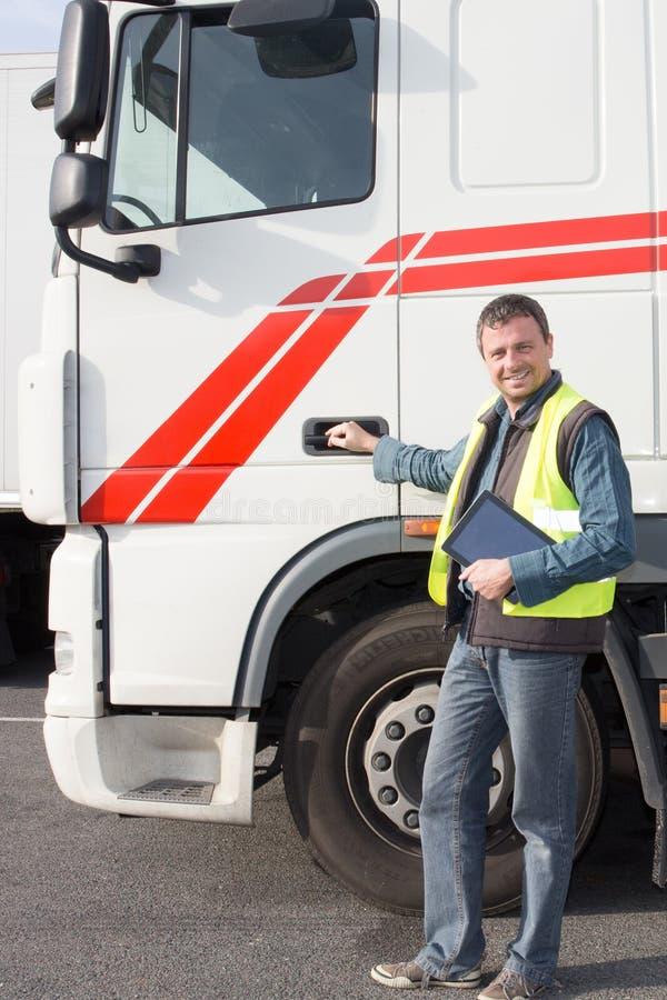 een volledige knappe vrachtwagenchauffeurarbeider vooraan vehicule stock foto's