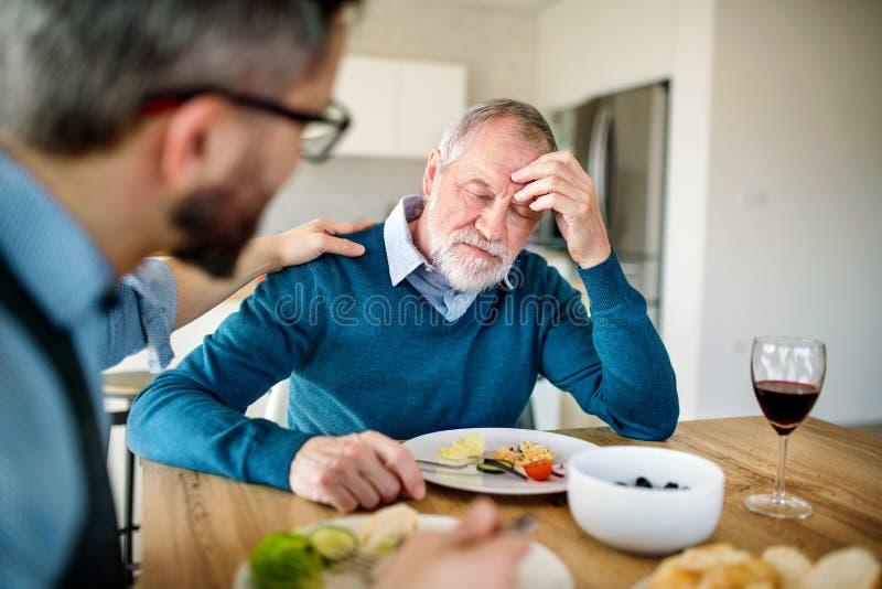 Een volwassen hipsterzoon en een gefrustreerde hogere vader die binnen thuis, lichte lunch eten stock afbeeldingen