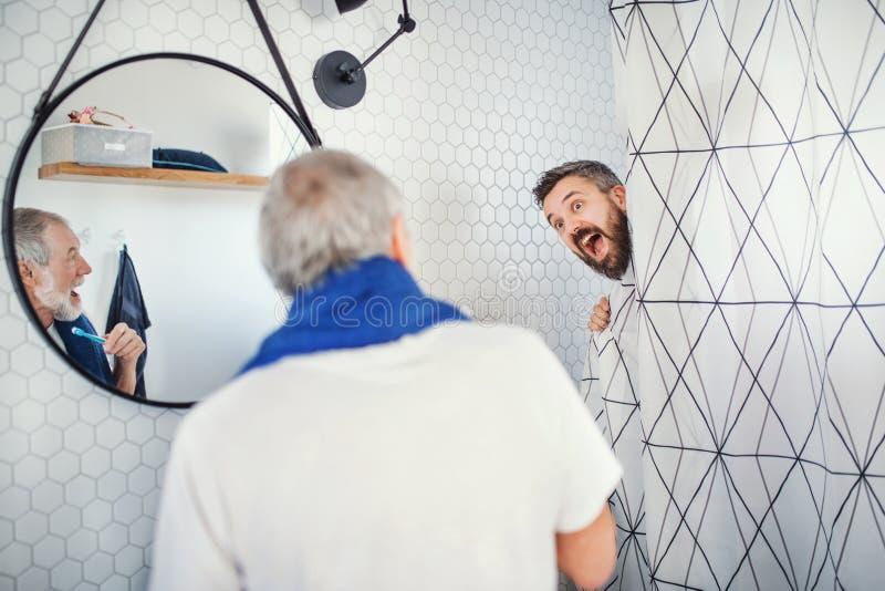 Een volwassen hipsterzoon en een hogere vader in badkamers binnen thuis, hebbend pret royalty-vrije stock foto