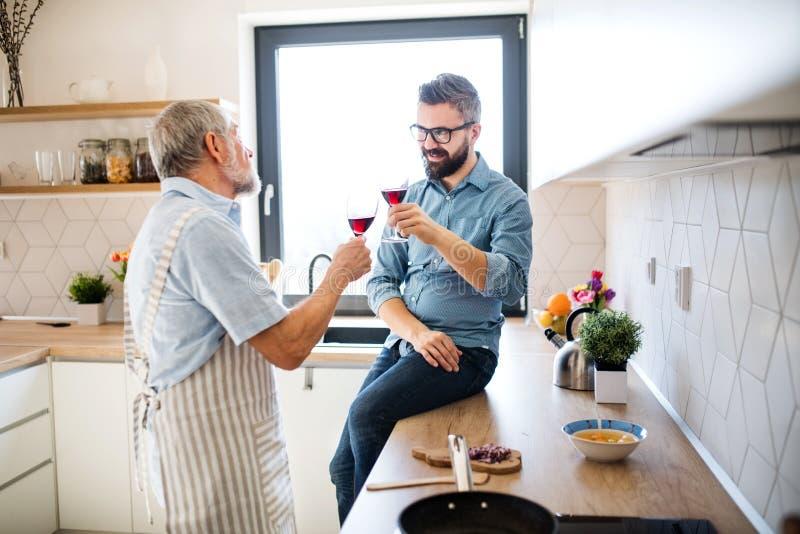 Een volwassen hipsterzoon en een hogere vader binnen in keuken die thuis, wijn drinken royalty-vrije stock foto's