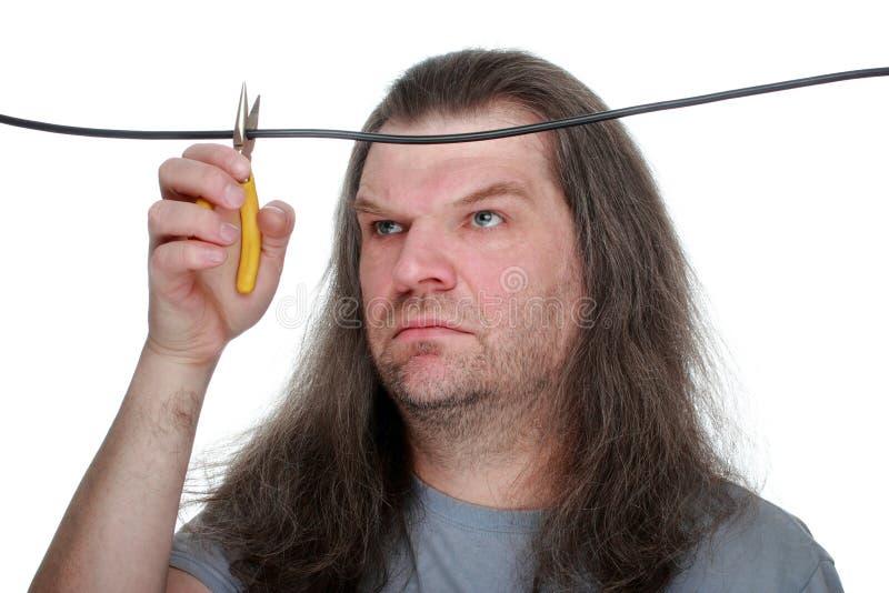 Een volwassen mens met lange haarsnacks de draad met draadscharen, g stock foto's
