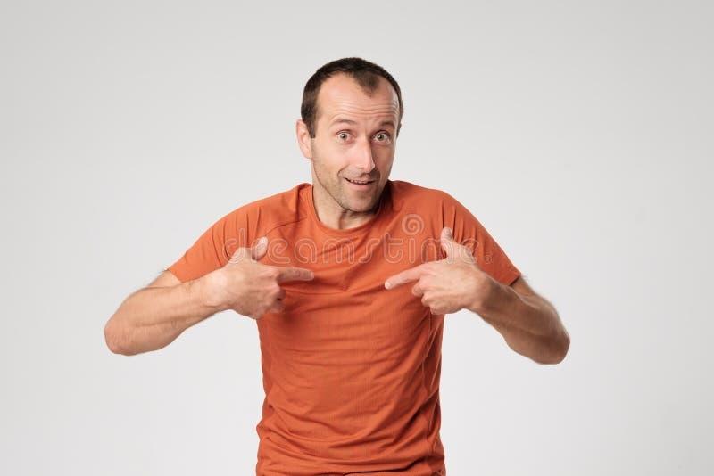 Een volwassen Spaanse mens in een oranje T-shirt richt aan zich met zijn vinger royalty-vrije stock fotografie