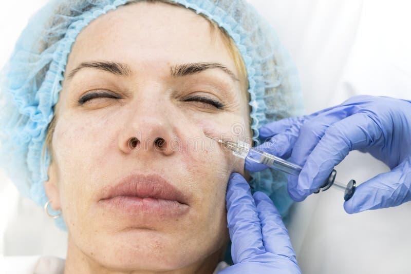 Een volwassen vrouw ondergaat kosmetische chirurgie stock foto