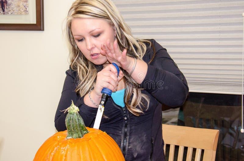 Een volwassen vrouw snijdt Halloween-pompoenen bij een lijst royalty-vrije stock foto