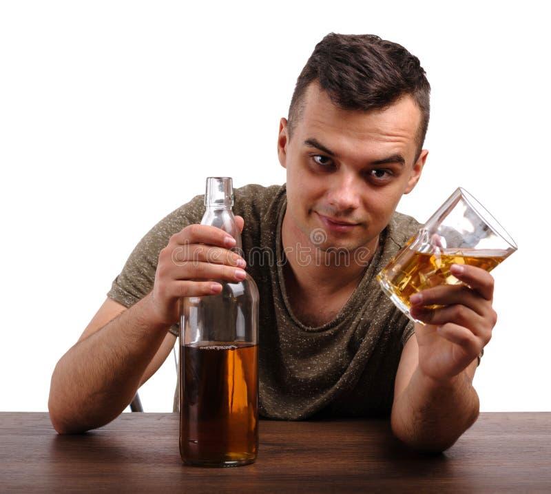 Een volwassene boozed de mens die een fles van een alcoholische drank tonen die, op een witte achtergrond wordt geïsoleerd Lege b stock afbeelding