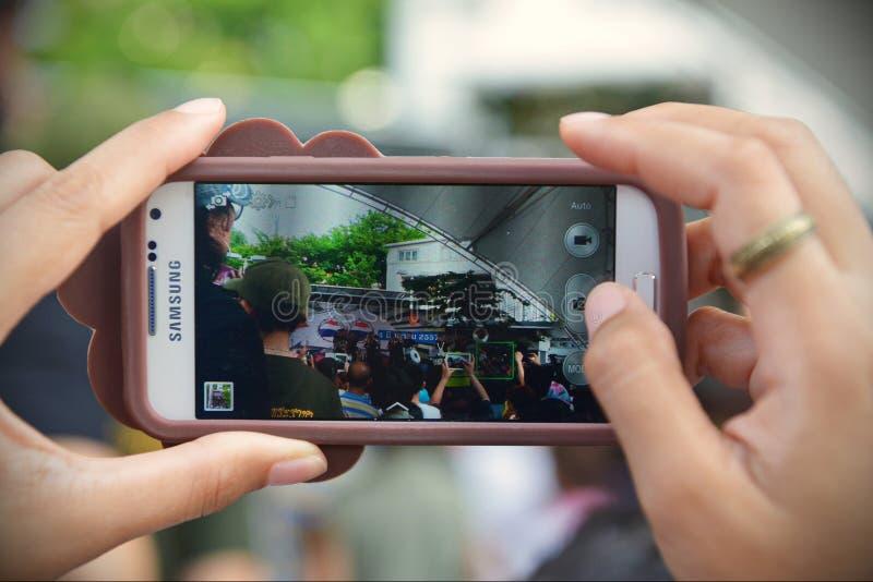 Een Voorbijganger gebruikt Smartphone om een Legergebeurtenis te vangen stock fotografie