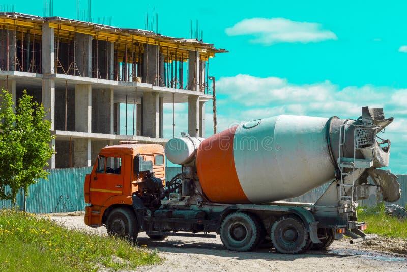 Een vrachtwagen is een vrachtwagen in aanbouw met een cabine van oranje kleur op een bouwwerf van een high-rise huis in de stad stock afbeelding