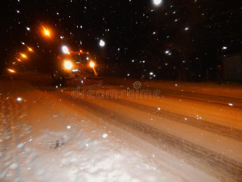 Een vrachtwagen met ploeg maakt de sneeuw op de weg schoon stock afbeeldingen