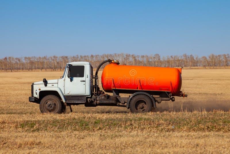 Een vrachtwagen voor het vervoer van benzine en brandstof met een oranje tankritten op een geel gebied op de weg tijdens de lever royalty-vrije stock afbeelding