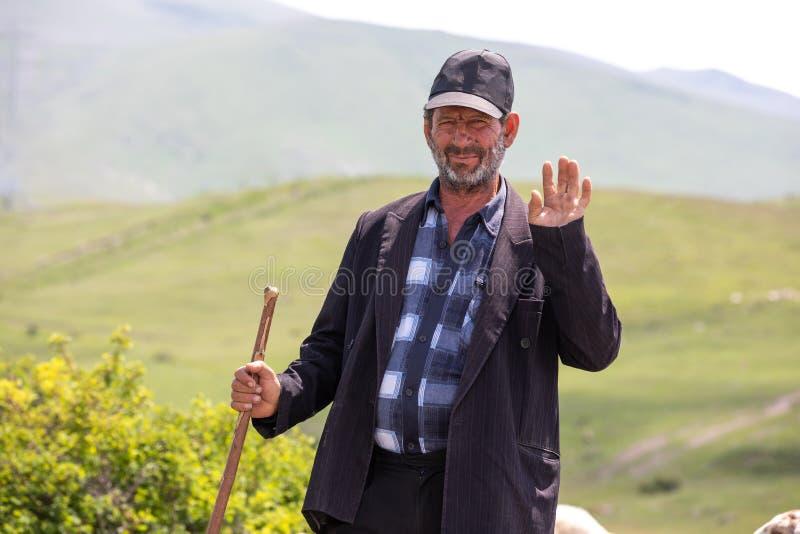 Een vriendschappelijk Armeens schaap die herder hello golven stock foto's