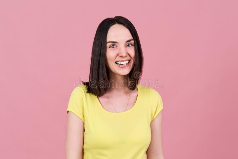 Een vriendschappelijk vrolijk donkerbruin meisje glimlacht wijd met een sneeuwwitte glimlach en bekijkt expressively de camera stock afbeelding