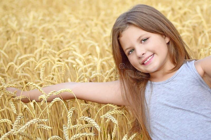 Een vrij gelukkig meisje wat betreft met de hand de gouden roggeoren op gebied Concept zuiverheid, de groei, geluk royalty-vrije stock foto