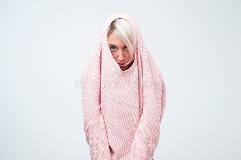 Een vrij Kaukasisch meisje met een sociale fobie verbergt haar gezicht in een sweater stock fotografie