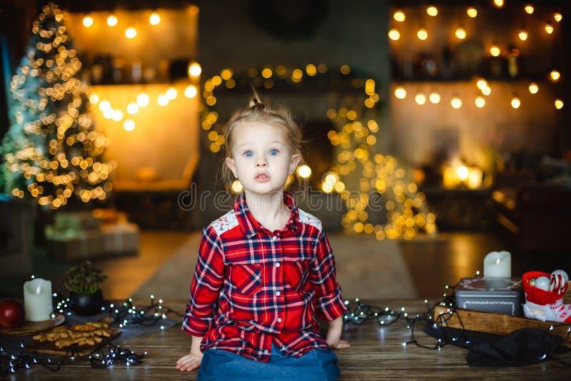 Een vrij weinig eyed blondemeisje zit op een houten lijst in een huis, met een Kerstboom en wacht op haar Kerstmisgift royalty-vrije stock afbeelding