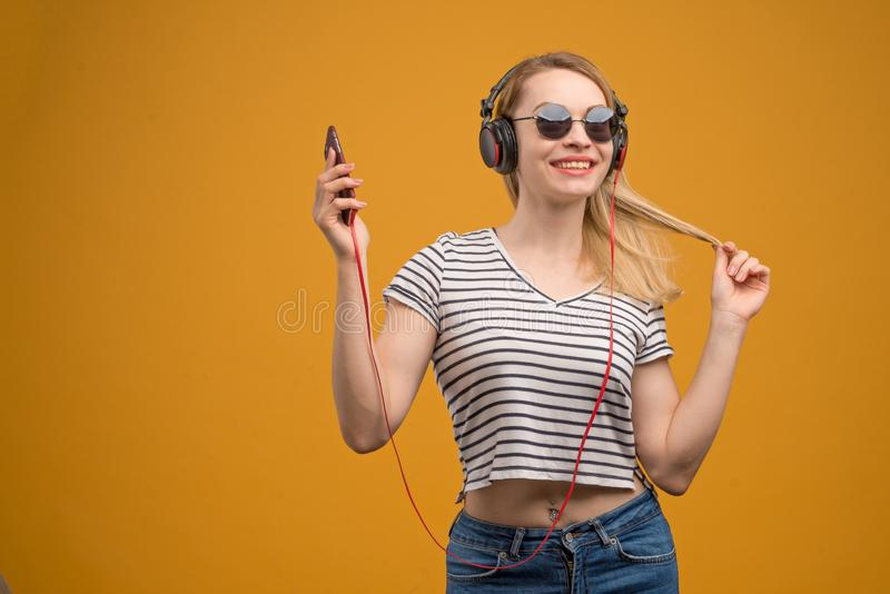Een vrolijk hipstermeisje die aan muziek op hoofdtelefoons met een telefoon op een gele achtergrond luisteren royalty-vrije stock foto