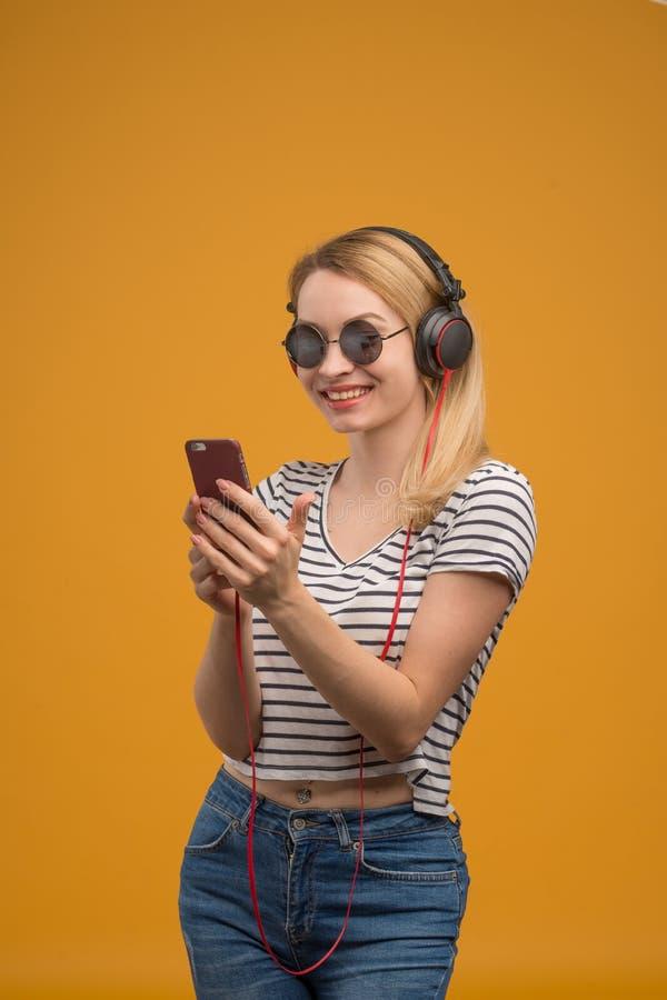 Een vrolijk hipstermeisje die aan muziek op hoofdtelefoons met een telefoon op een gele achtergrond luisteren royalty-vrije stock fotografie