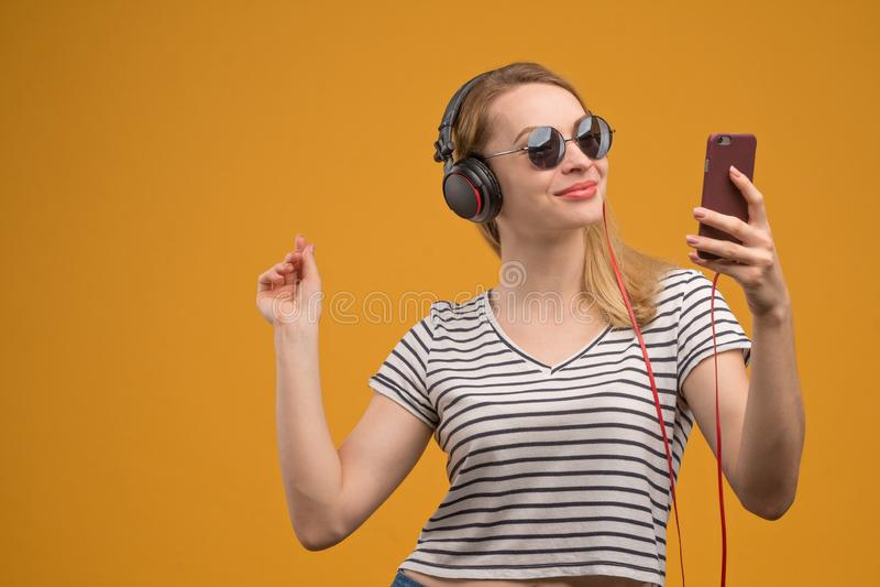 Een vrolijk hipstermeisje die aan muziek op hoofdtelefoons met een telefoon op een gele achtergrond luisteren stock afbeelding